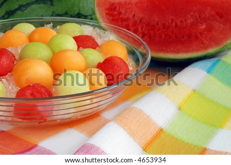 bowl of melon balls on crushed ice displayed on color coordinated tablecloth with seedless watermelon in the background - stock photo
