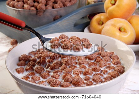 Bowl of milk and chocolate cereal with a spoon - stock photo