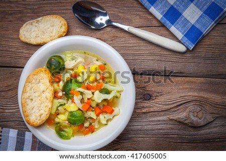 Bowl of minestrone soup on wooden table. - stock photo