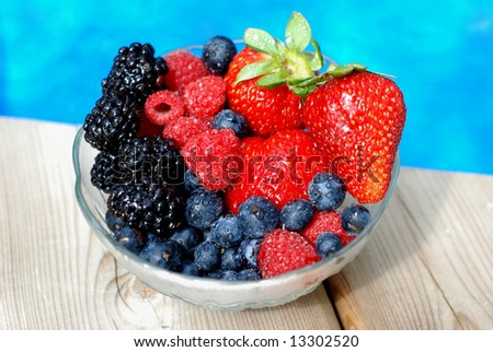 Bowl of mixed berries on a wooden deck near a pool - stock photo