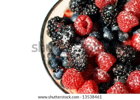 Bowl of mixed berries with sugar on top - stock photo