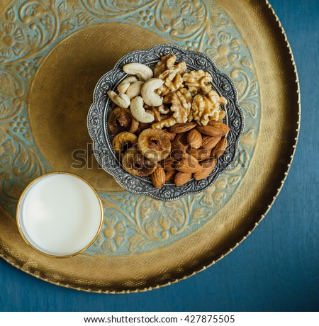Bowl of mixed nutritious nuts and glass of fresh milk. A healthy food for breaking Ramadan Fast. - stock photo