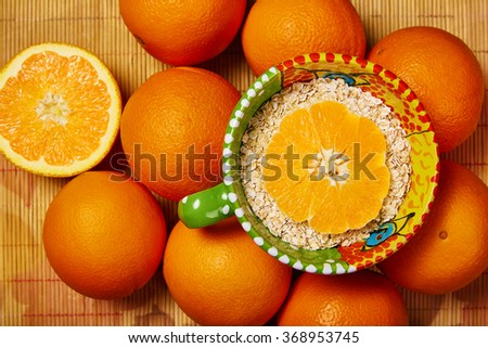 Bowl of muesli with fresh oranges / Overhead view / Top view - stock photo