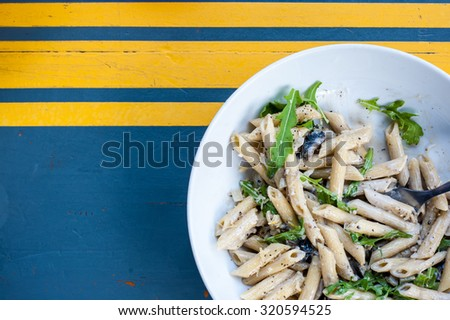 Bowl of mushroom and rocket penne pasta on a blue and yellow painted wood background - stock photo