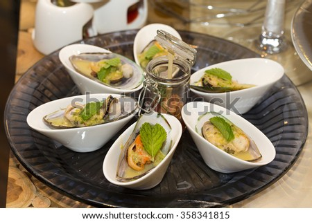 Bowl of mussels on the wooden table - stock photo