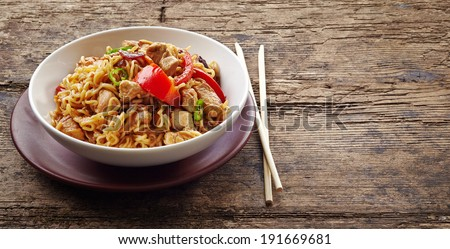 bowl of noodles with chicken and vegetables on wooden table - stock photo