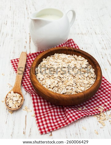 bowl of oat flake and milk on a wooden background - stock photo