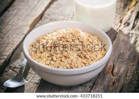 Bowl of oat flakes and glass of milk, on wooden surface. - stock photo