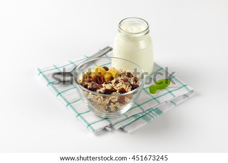 bowl of oat flakes and glass of white yogurt on checkered dishtowel