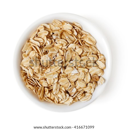 Bowl of oat flakes isolated on white background, top view - stock photo