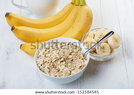 Bowl of oat flakes with sliced banana close-up on wooden table - stock photo
