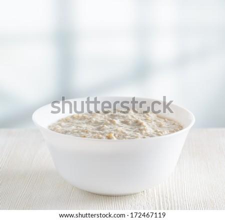 Bowl of oat porridge on wooden table. - stock photo