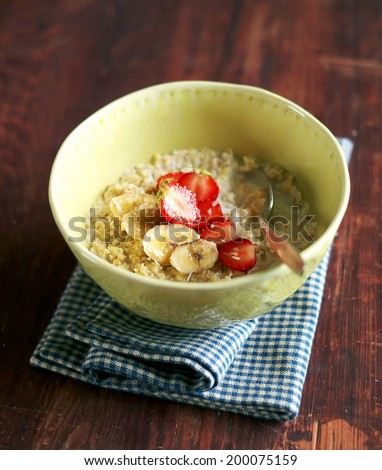 Bowl of oatmeal porridge served with fresh chopped strawberry, banana slices and freshly shredded coconut for morning breakfast or healthy snack, selective focus - stock photo