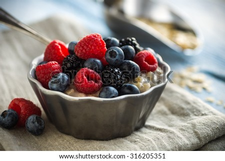Bowl of oatmeal porridge with mixed berries - stock photo