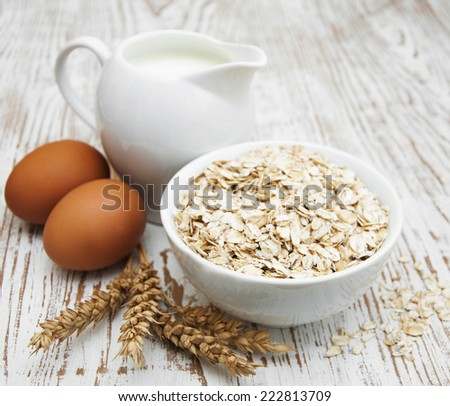 Bowl of oats on a old wooden background - stock photo