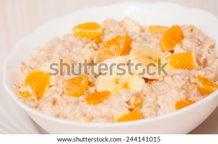 Bowl of oats porridge with banana and tangerine - stock photo