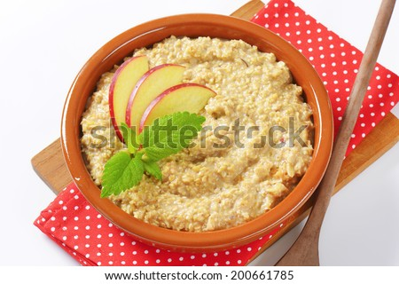 Bowl of oats porridge with fresh apple - stock photo