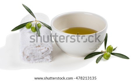 Bowl of olive oil,and towel decorated with green olive fruit isolated on white background. Hands Spa. Manicure concept.