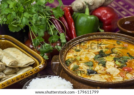 Bowl of panang curry stew surrounded with vegetables and spices - stock photo