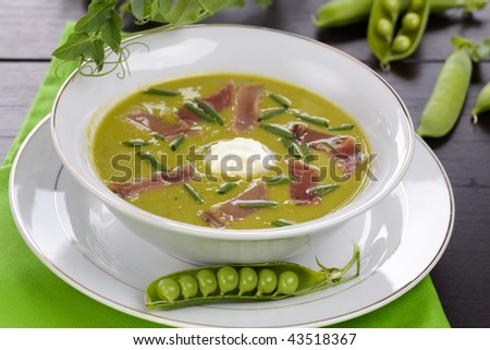 Bowl of pea soup with prosciutto garnished with chives. Sprig of flowering pea and cracked pea pods.