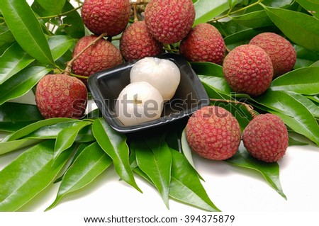 Bowl of peeled lychee with leaf on white - stock photo