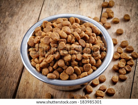 Bowl of pets food on wooden floor - stock photo