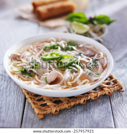 bowl of pho with beef, bean sprouts and peppers - stock photo