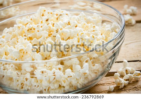 Bowl Of Popcorn - This is a shot of a glass bowl full of hot air popped popcorn on a wooden table. Shot with a shallow depth of field. - stock photo