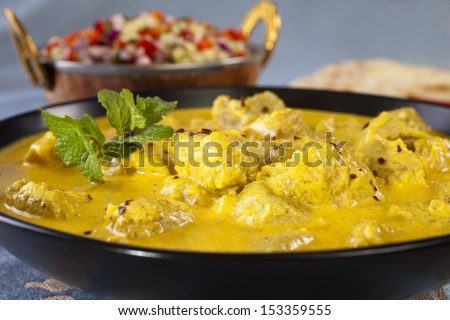 Bowl of pork curry in a creamy sauce flavoured with garlic, cinnamon, coriander, cumin, turmeric and chilli, served with kachumber Indian salad and naan bread.  - stock photo
