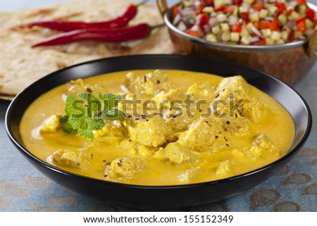 Bowl of pork curry in a creamy sauce flavoured with garlic, cinnamon, coriander, cumin, turmeric and chilli, served with kachumber Indian salad and naan bread. Could be chicken. - stock photo