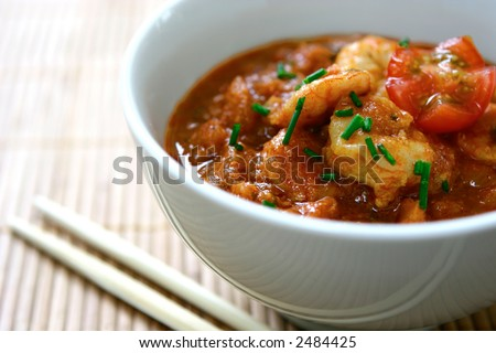 Bowl of prawn masala curry in white bowl, served on oriental table mat.