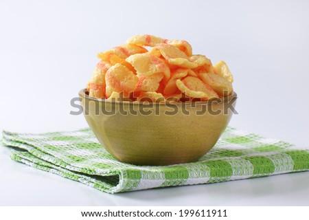 bowl of puffed cornmeal crisps - stock photo