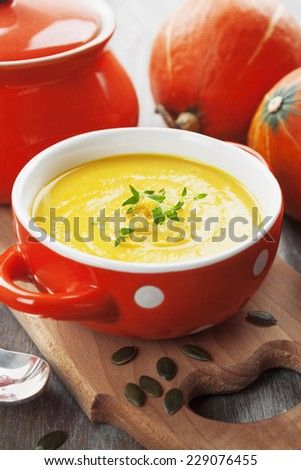 Bowl of pumpkin soup on a wooden table
