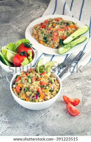 Bowl of quinoa with vegetables, tomatoes and cucumbers  - stock photo