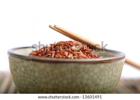 Bowl of red rice from Thailand and chopsticks. - stock photo