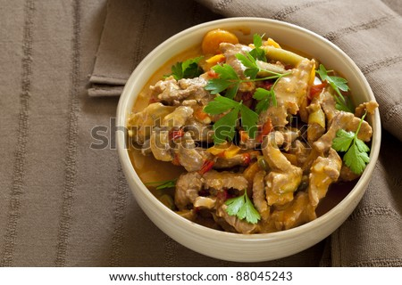 Bowl of red Thai beef curry, over brown linen. - stock photo