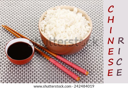 Bowl of rice and chopsticks and space for your text on grey mat - stock photo