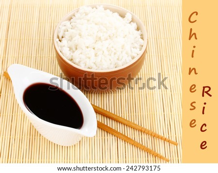 Bowl of rice and chopsticks on bamboo mat with space for your text - stock photo