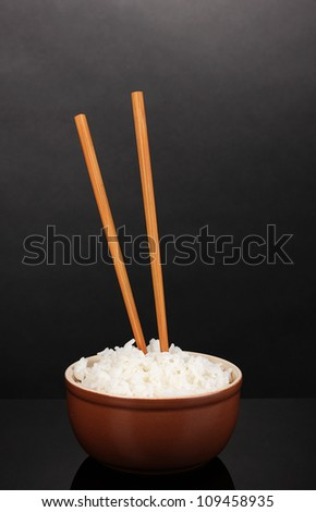 Bowl of rice and chopsticks on grey background - stock photo