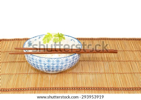 Bowl of rice with chopsticks decorated with fried onions and coriander against white background - stock photo