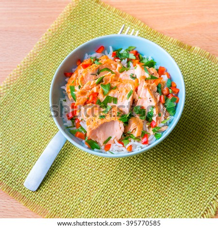 Bowl of rice with poached salmon and vegetables. - stock photo