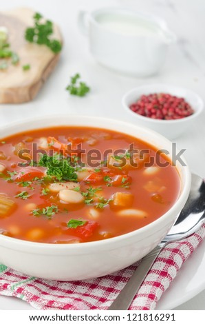 bowl of roasted tomato soup with beans, celery and bell pepper, pink pepper and sour cream in the background - stock photo