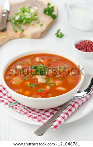 bowl of roasted tomato soup with beans, celery and sweet pepper garnished with fresh parsley, pink pepper and sour cream in the background - stock photo