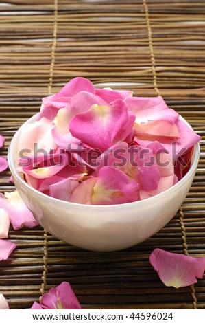 Bowl of rose petals on bamboo mat - stock photo