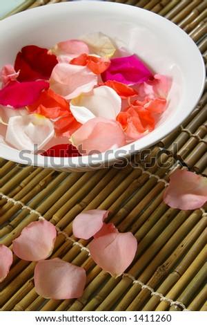 Bowl of rose petals on bamboo spa mats. - stock photo