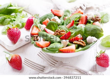 bowl of salad with strawberry, spinach leaves and feta cheese on wooden table
