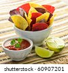 Bowl of salsa with colorful tortilla chips and lime - stock photo