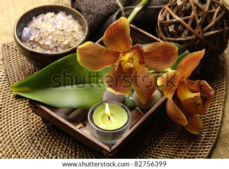bowl of salt and candle in basket and orchid with towel with on burlap mat - stock photo