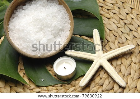 bowl of salt with seashell and monstera leaf on woven mat - stock photo