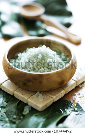 bowl of scented bath-salt, surrounded by banana leafs - stock photo